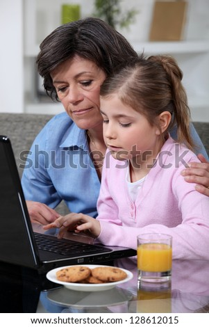 Child and her grandmother using a laptop - stock photo
