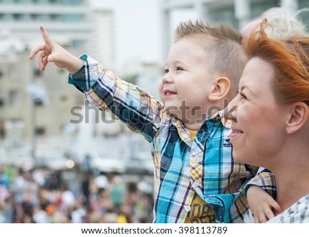Child and his mother watching the air show dedicated to Israel's Independence Day in the Tel Aviv promenade. Stock image photo. Tel Aviv, Israel, May 2014. - stock photo