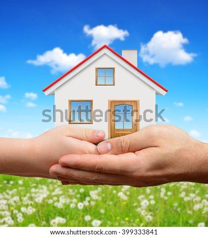 Child and male hands holding house - stock photo