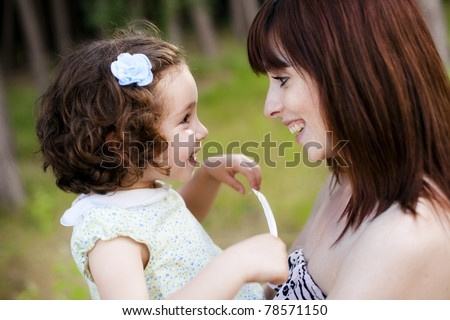 Child and mom looking and smiling each other - stock photo