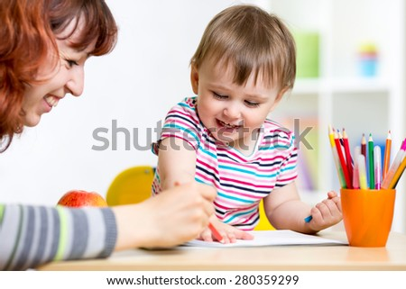child and mother drawing with colorful pencils - stock photo