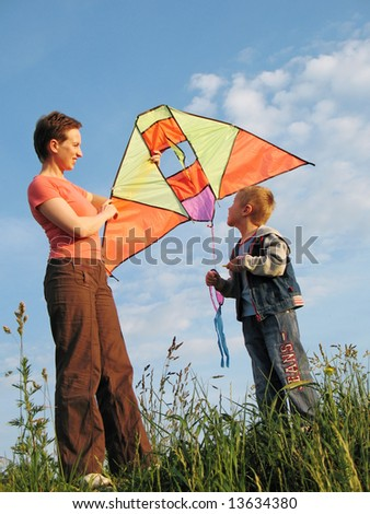 child and mother fly a kite