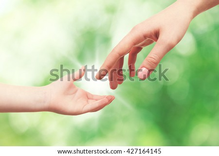 Child and mother hands on green nature background. Concept of taking care, protection, helping and assistance - stock photo