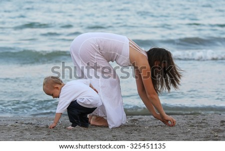 Child and mother looking for sea shells in the sand on the beach - stock photo