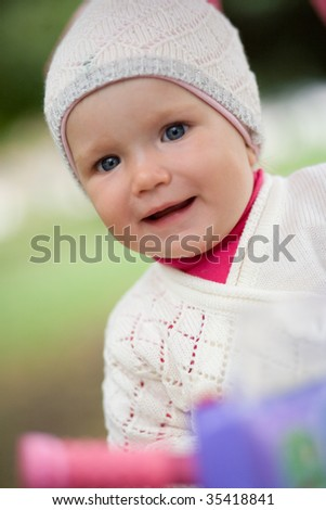 Child and mother on walk in park. The child on a bicycle. - stock photo