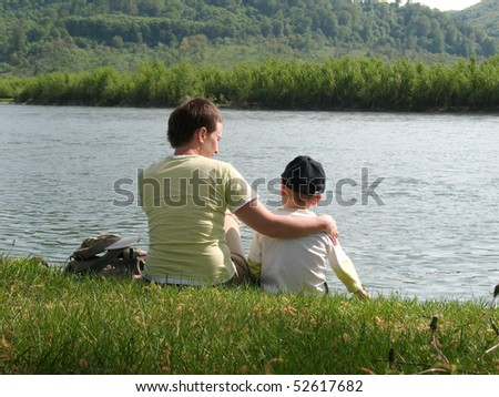 child and mother sitting on river shore - stock photo