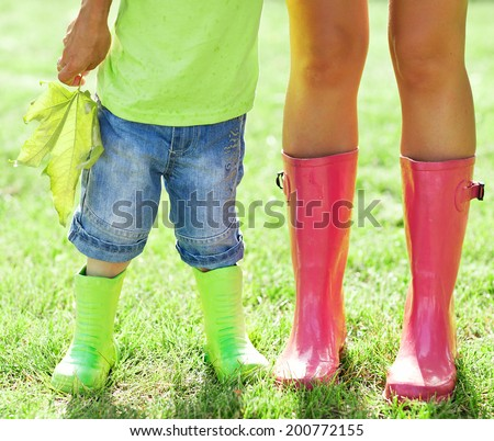Child and mother wearing pink and green rain boots