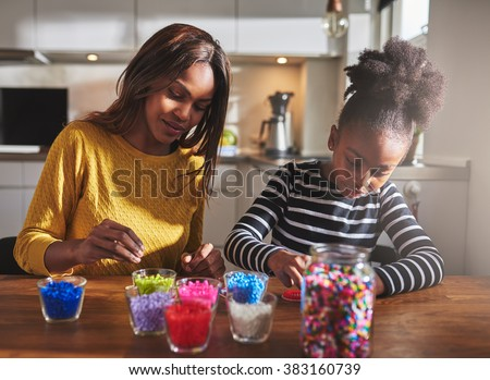 Child and parent sitting and creating color beaded crafts on wooden table in kitchen with various jars in front of them - stock photo
