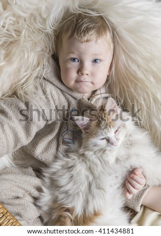 Child and pat. Cute Boy hugging cat at home. Bedding and textile for infant nursery. - stock photo
