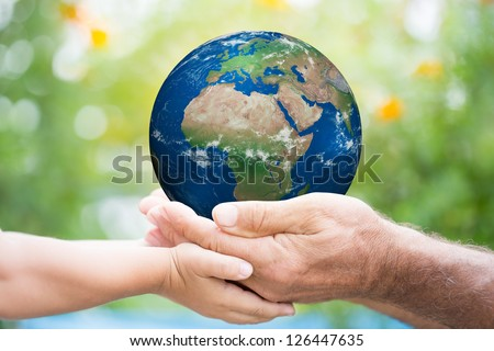 Child and senior man holding planet Earth in hands against green spring background. Elements of this image furnished by NASA - stock photo