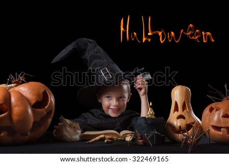 Child and spooky Halloween pumpkin with magic book, candle, spider on black background - stock photo