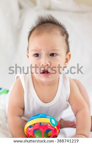 child and toddler concept - curious baby sitting on bed and look - stock photo