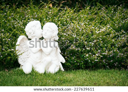Child angel statue in a park. - stock photo