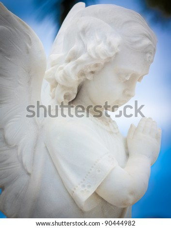 Child angel statue with a blue sky background - stock photo