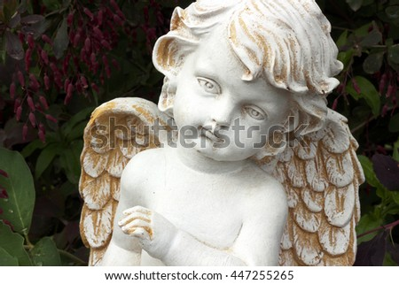 Child angel statue with bush barberry background. Close-up - stock photo