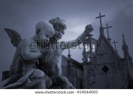 Child angels statue  with a lamp in the hand of an old european cemetery at night or dusk