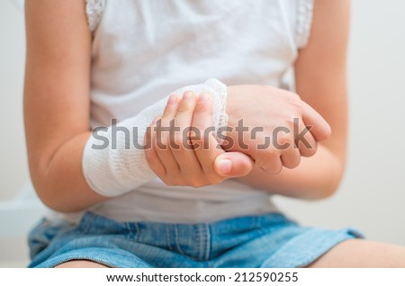 Child arm with gauze bandage on it. - stock photo