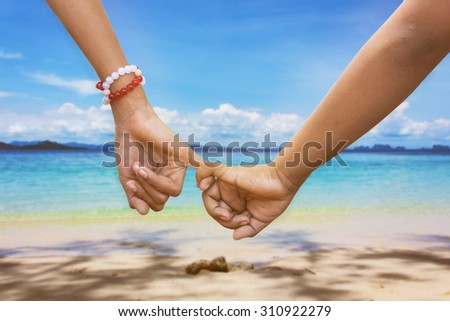 child asian girl couple in love holding hands in the beach background