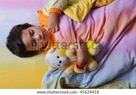 Child asleep, in bed, dark - stock photo