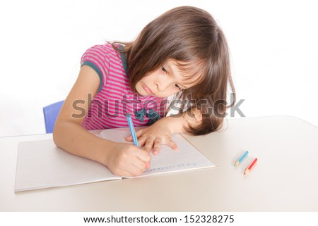 Child at desk with pencils and notebook - stock photo