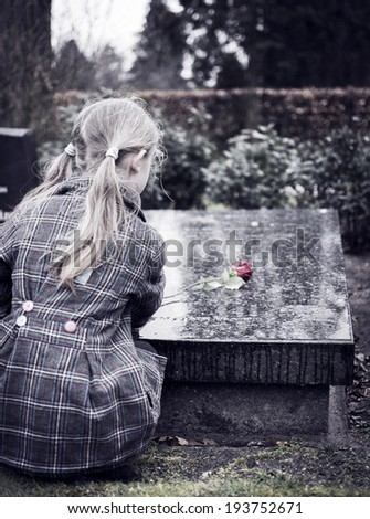 Child at graveyard grieving for loss of family or friend - stock photo