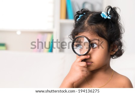Child at home. Cute Indian girl peeking through magnifying glass. - stock photo