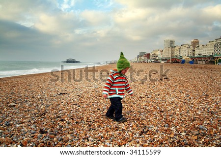 child at seaside on beach in brighton with old pier in background. holiday vacation resort in sussex in england - stock photo
