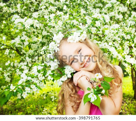 Child at spring. Happy girl outdoors. Blooming apple tree - stock photo