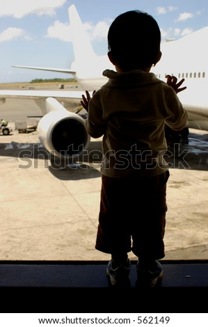 Child at the airport looking outside. - stock photo