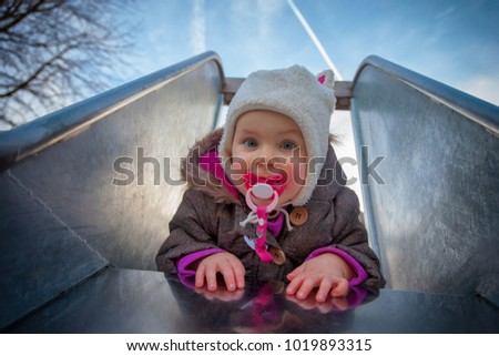 child at the playground sliding on a slide