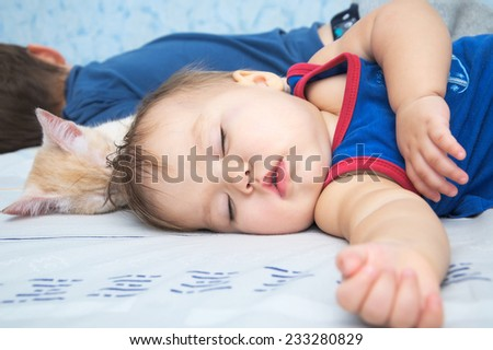 Child baby sleeping daytime with brother and cat - stock photo