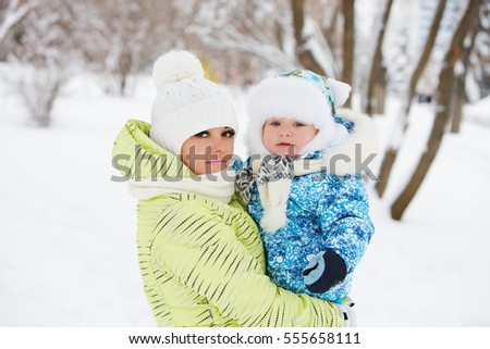 child baby with mother on a winter walk in nature.