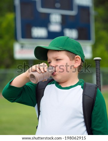 Child baseball player drinking chocolate milk after game - stock photo
