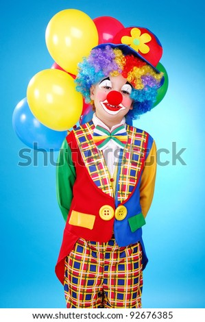 Child birthday clown with balloons over the blue background - stock photo