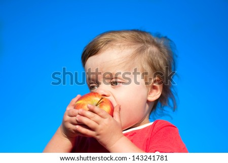 child bite off juicy big apple against the background sky
