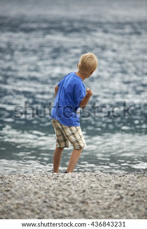 Child blond boy throwing pebbles into the sea - stock photo