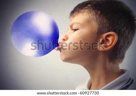 Child blowing a blue bubble gum - stock photo