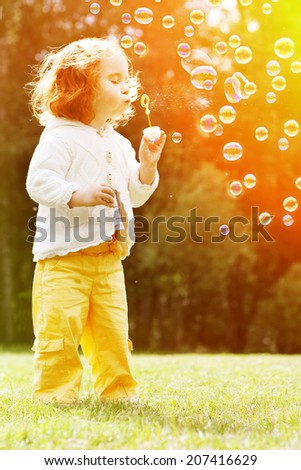 Child blowing a soap bubbles. Kid blowing bubbles on nature. Baby at sunset, the sun's rays - stock photo
