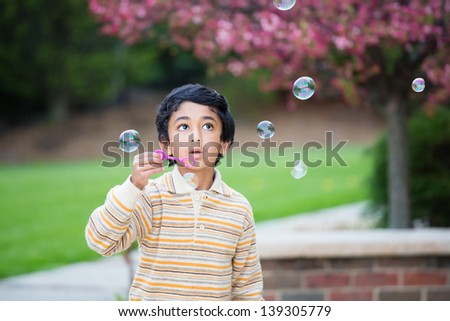 Child Blowing Bubbles in the Yard in Spring - stock photo
