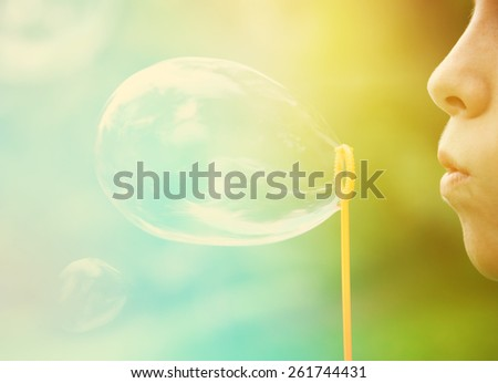 Child blowing bubbles.  Instagram effect.  Focus on lips and edge of bubble wand. - stock photo