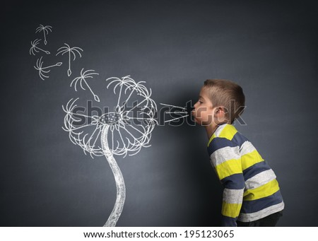 Child blowing dandelion seeds on a blackboard concept for wishing, hope and aspirations - stock photo