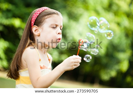 Child blowing soap babbles in the park - stock photo