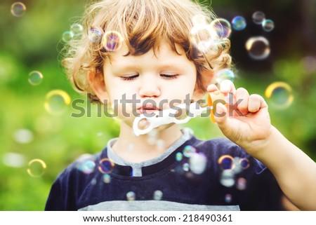 Child blowing soap bubbles, closeup portrait beautiful  baby. - stock photo