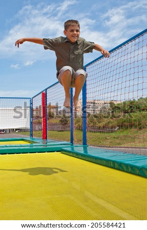 Child bouncing on a trampoline outdoors - stock photo