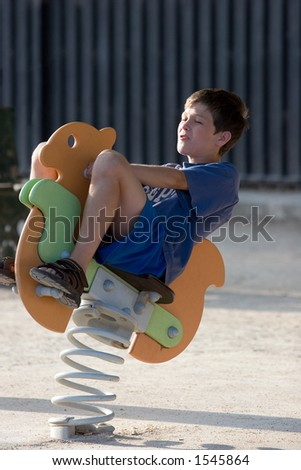 Child bouncing on horse toy - stock photo