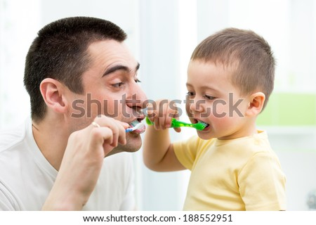 child boy and his dad brushing teeth in bathroom - stock photo