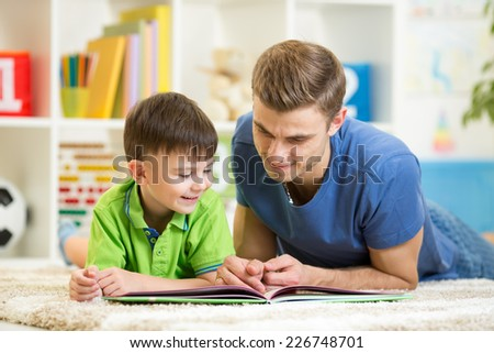 child boy and his dad read a book on floor at home - stock photo