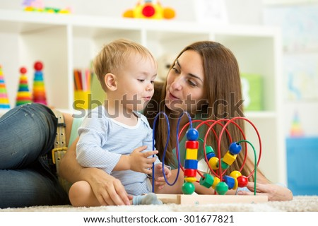 child boy and mother playing with educational toy - stock photo