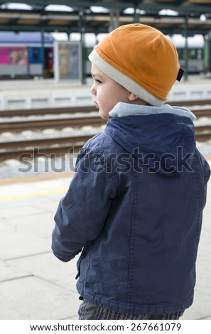 Child boy at train station platform  waiting for a train, back view.