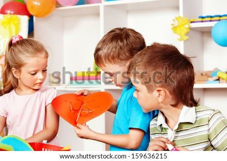 Child boy cutting out scissors paper heart